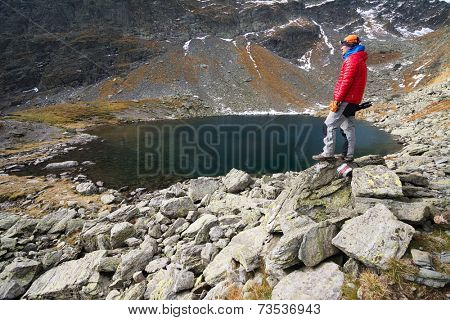 Alpinist on the shore of an alpine lake