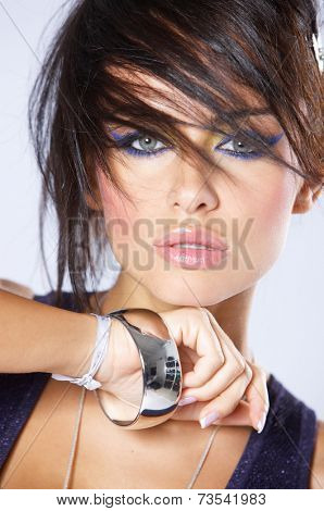 Close up Beautiful Young Woman in Funky Hair with Silver Bracelet Isolated on Gray Background.