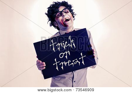 a gap-toothed zombie showing a black signboard with the text trick or treat written in it, with a retro effect