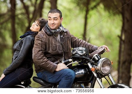 Happy active family posing on beautiful modern bike, wearing stylish leather jacket, extreme sport, traveling and freedom concept