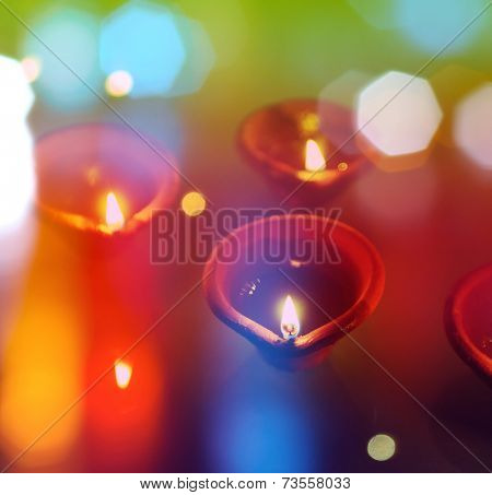 An abstract colorful Diwali greeting card cover with traditional diyas.