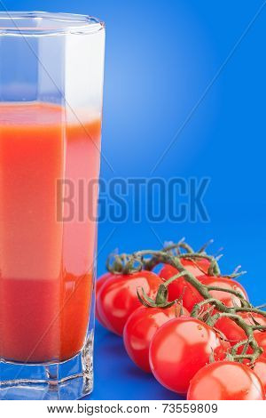 Faceted Glass Of Tomato Juice And Branch Of Cherry Tomatoes