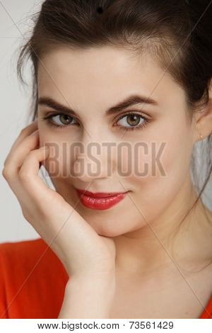 Smiling Pretty Woman In Orange With Hand On Face