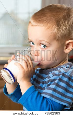 Young Boy Drinking Milk Out Of Glass