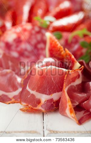 antipasti Platter of Cured Meat,   jamon, sausage, salame  on textured white wooden table