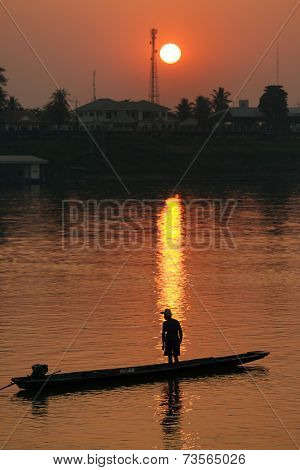 Sunset on Mekong river with man silhouette, on a small wooden boat, Vientiane, Laos