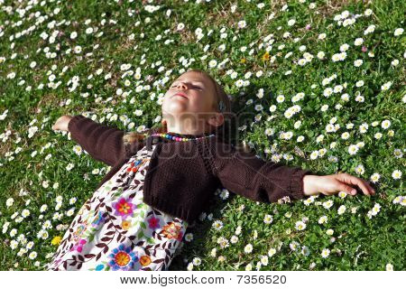 Girl sleeping in field of daisies