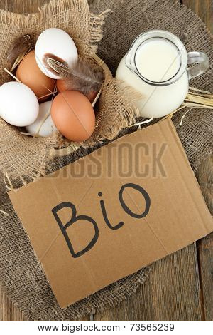 Eggs and fresh milk in glass jug with inscription BIO  , on wooden background. Organic products concept