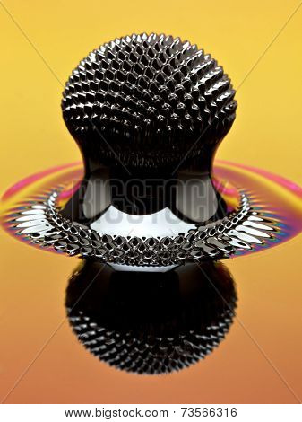 Ferrofluid structure induced by a neodymium magnet reflecting colorful lights