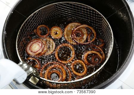 Onion in deep fryer, closeup