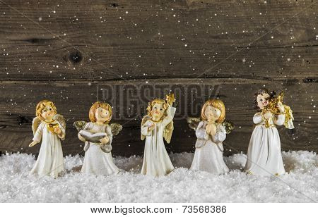 Christmas decoration with angels on wooden snowy background for a greeting card.