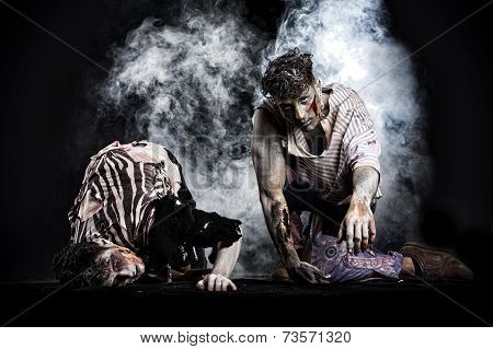 Two Male Zombies Crawling On Their Knees, On Black Smoky Background