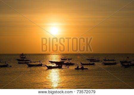 silhouettes of fishing boats at sunset in Bali.