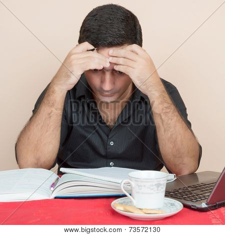 Adult education - Tired hispanic man studying at home