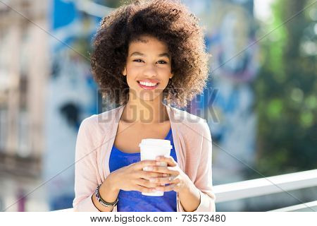 Afro woman with coffee to go