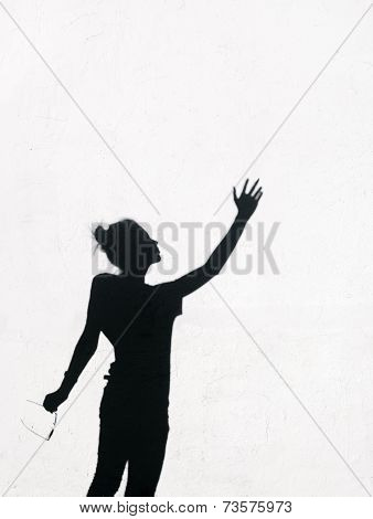 Girl Stretching Her Hand Toward The Sky Around On The White Wall Background