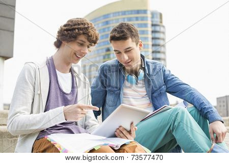 Happy young male college students using digital tablet against building