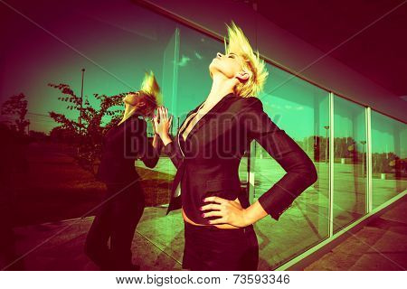 elegant young  woman with short blonde hair in black blazer throw back hair shot in the city by the glass wall