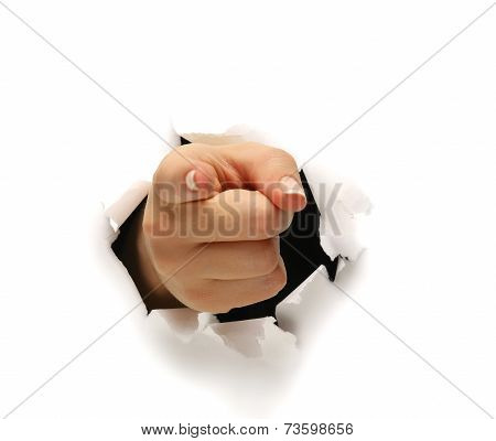 A female hand breaking through paper pointing at you.