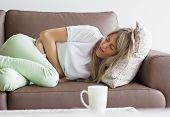 stock photo of stomach  - Woman having stomach pain, lying down on couch