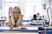 picture of self-employment  - Young self employed fashion designer taking customer orders by phone - JPG