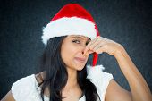 picture of fart  - Closeup portrait of pretty young woman in santa claus hat closing covering nose something stinks isolated gray black background - JPG