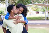 stock photo of human face  - Closeup portrait of a young couple guy giving woman piggy back ride and kissing face happy moments positive human emotions on isolated outdoors outside park background - JPG