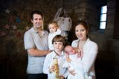 image of baptism  - Happy Young Family With Three Children Celebrating The Baptism Of Their Newborn Baby Son - JPG