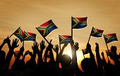 picture of waving  - Group of People Waving South African Flags in Back Lit - JPG