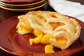 stock photo of crust  - half of a peach pie with a lattice crust on a serving plate - JPG
