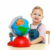 picture of montessori school  - Little girl sitting at the table and looks at a globe - JPG