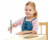 picture of montessori school  - Little girl draws pencils sitting at the table - JPG