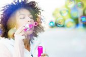 stock photo of afro  - Afro woman blowing soap bubbles  - JPG