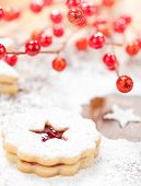 stock photo of linzer  - Christmas Linzer cookie with powdered icing sugar and red decorations in the background - JPG