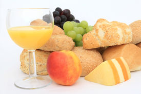 stock photo of continental food  - Wholesome healthy breakfast food, bread, cheese, red and green grapes, orange juice, isolated on white, copy space, shallow depth of field. ** Note: Shallow depth of field - JPG