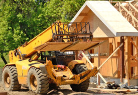 picture of boom-truck  - A roofing contractor moves plywood sheeting at a commercial residential development using a telehandler forklift truck - JPG