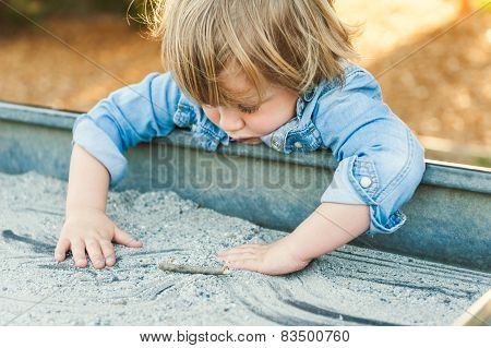 Adorable toddler boy playing in a sand box