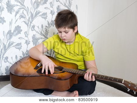 Teenage Boy plays an acoustic guitar