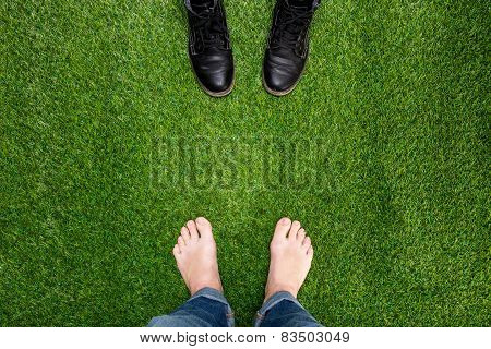 Mens Feet Resting On Green Grass Standing Opposite Boots