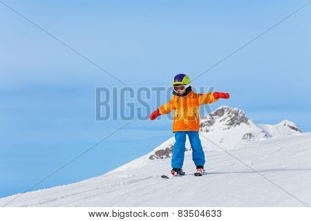 Boy with ski mask and arms apart skiing in winter