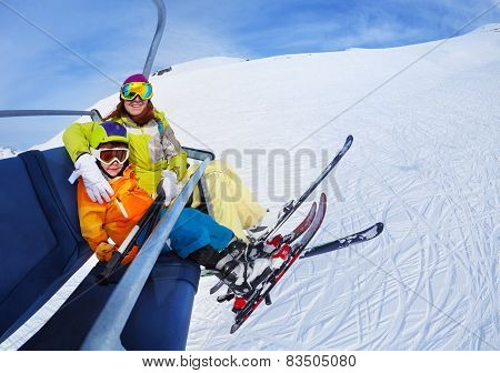 Little skier boy with mother lift on mountain