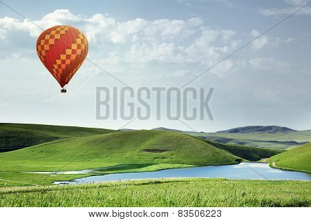 Air Balloon Flying Over The Meadows With Lake