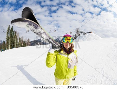 Young woman carry mountain ski on winter resort