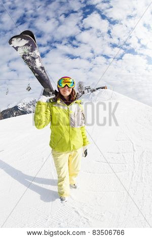 Young woman going mountain ski on winter resort