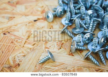 Screws closeup on wooden background