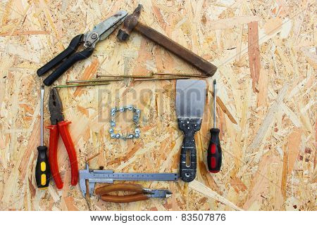 Construction tools in the form of house on wooden background. construction tools: pliers, hammer, pr