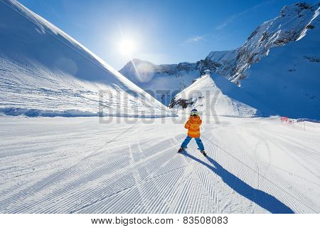 Boy on ski-track skiing view from back in Sochi