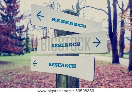 Rural Signboard With The Word Research With Arrows Pointing In Three Directions