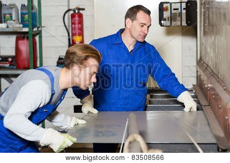 Two Workers Bending Sheet Metal With Large Machine