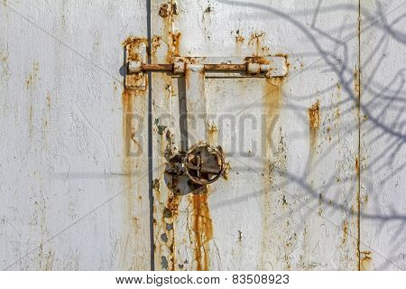 Rusty Wall Of A Metal Hut With Corroded Bolts And Padlock